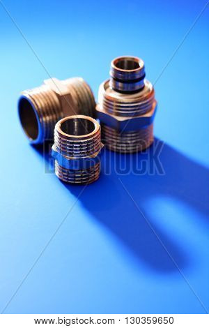 Set of metal clutches on blue background with shadow