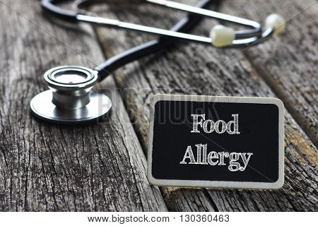 Medical Concept- Food Allergy word written on blackboard with Stethoscope on wood background