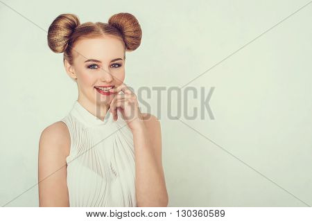 Close-up portrait happy beautiful girl with funny hairstyle. Sly and scheming young woman face expression.