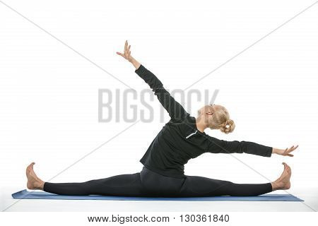 Incredible blonde girl in the sportswear makes the splits on a blue gymnastic mat on the white background in the studio. She wears black pants and black long sleeve t-shirt. She is barefoot. She stretched her arms to the sides. Photographed from the back.