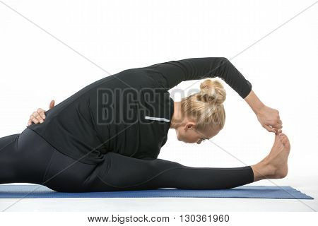 Girl in the sportswear makes the splits on a blue gymnastic mat on the white background in the studio. She wears black pants and black long sleeve t-shirt. She is barefoot. She clasps her left hip with right hand, left hand holds the right toe. Photograph