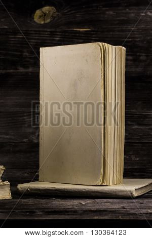 stacked books on  wooden background place for text