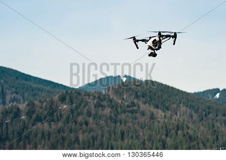 Drone with camera hovering over mountains low angle view
