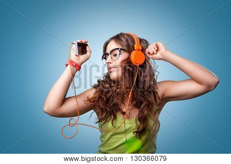 Beautiful girl with long curly hair in headphones and glasses with closed eyes listening to music and dancing. Portrait girl on blue background. Human facial expressions emotions feelings.