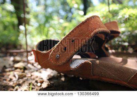 soft leather sandals on a background of stones and leaves