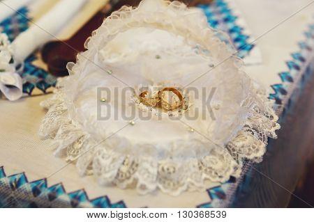 Two luxury golden wedding rings on white cushion closeup