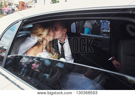 Happy Romantic Newlyweds Kissing In Wedding Limo
