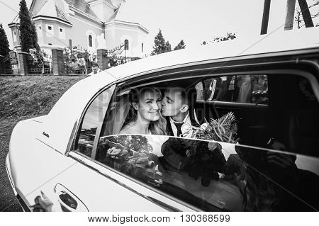 Happy Romantic Newlyweds Kissing In Wedding Limo B&w