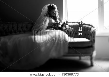 Romantic Princess Blonde Bride With Bouquet Posing On Sofa B&w