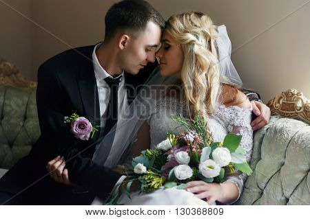 Romantic Sensual Newlyweds Posing On Luxury Sofa With Bouquet