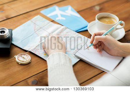 vacation, tourism, travel, destination and people concept - close up of traveler hands with blank notepad and pencil