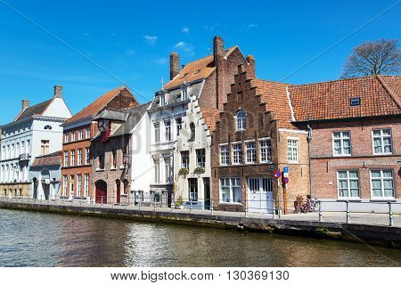 Bruges, Belgium - April 10б 2016: Panorama with canal and colorful traditional houses against blue sky in Brugge, Belguim