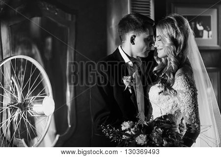 Romantic Newlyweds Posing In Dark Rustic Red Restaurant Room B&w