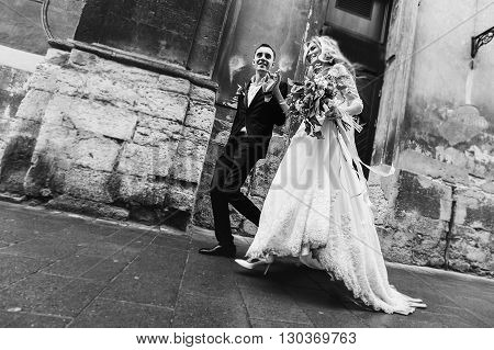 Romantic Newlyweds Walking Down Old European Street B&w