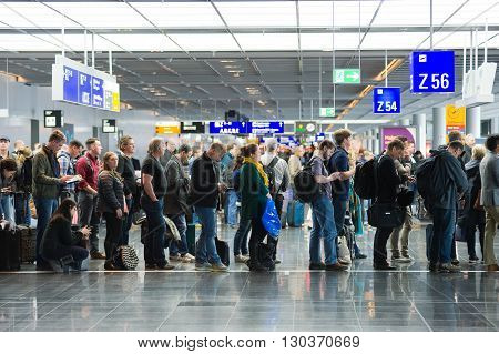 FRANKFURT GERMANY - APRIL 25 2016: Passengers waiting in a row for boarding on an airport to a flight to America