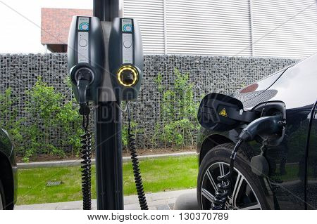 HENGELO THE NETHERLANDS - MAY 17 2016: An electric car is parked at a parking spot and is being recharged at a power station.
