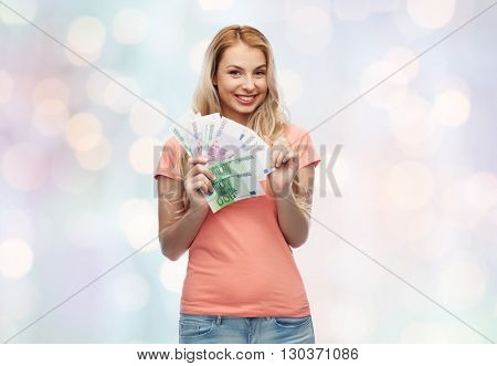 money, finances, investment, saving and people concept - happy young woman with euro cash money over blue holidays lights background