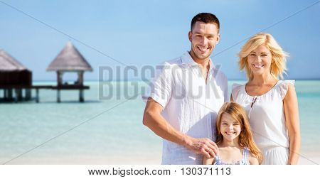 summer holidays, travel, tourism, vacation and people concept - happy family over exotic tropical beach with bungalow hut background
