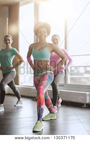 fitness, sport, training, gym and lifestyle concept - group of happy women working out and stretching leg in gym