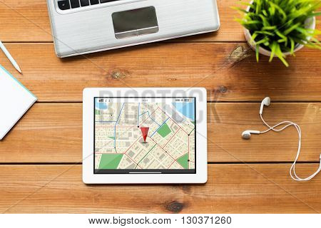 navigation, location, business and technology concept - close up of tablet pc computer, laptop and earphones on wooden table with gps navigator map
