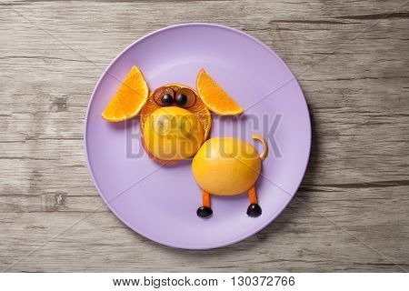 Funny pig made of orange and grape on plate and wood