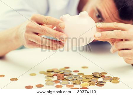 business, people, finances, crisis and money saving concept - close up of businessman pouring coins from piggy bank at office