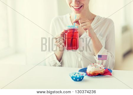independence day, celebration, patriotism and holidays concept - close up of happy woman eating glazed sweet donut, drinking juice from glass mason jar or mug and celebrating 4th july at home party