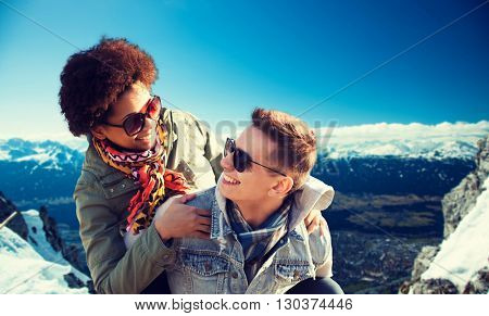 friendship, travel, tourism and people concept - happy international teenage couple in shades having fun over alps mountains in austria background