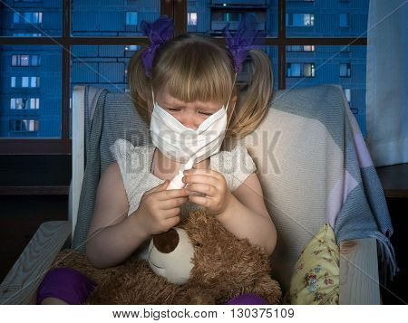 Little girl in medical mask holding a bottle of drops and crying. On lap toy bear. The house, in the evening, the windows of houses, the city. Conceptually about diseases, infections and allergies