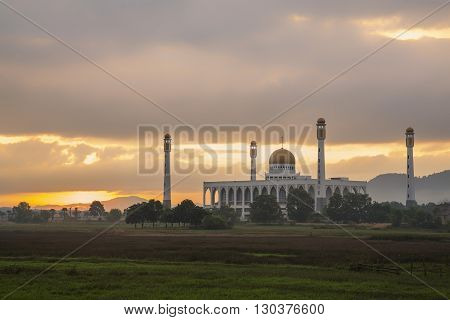 Beautiful mosque on green field with sunrise