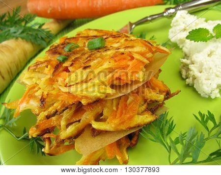 Homemade oancakes with carrots and parsnips on plate