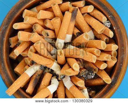 cigarette filter in ceramic ashtray on blue table