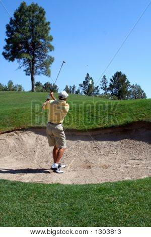 Golfer Successfully Hitting Golf Ball Out Of A Sand Trap