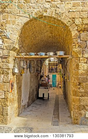 ACRE ISRAEL - FEBRUARY 20 2016: The arched pass to the medieval yard is decorated with the used cookwares on February 20 in Acre.