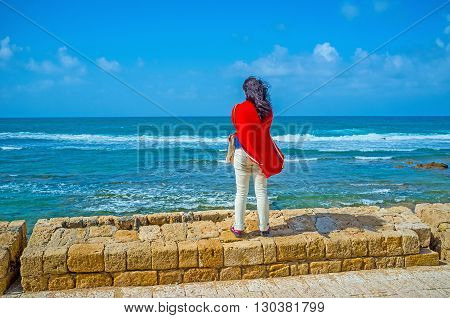 Young girl enjoy the seascape watching the white waves standing on the ruins of old rampart Acre Israel.