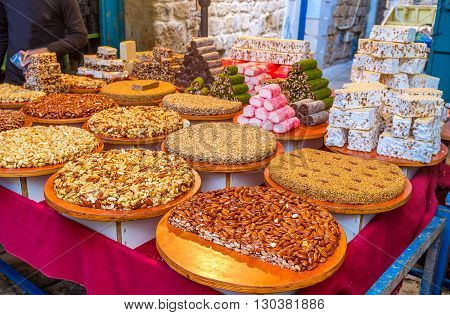 The gozinaki made of nuts sesame and sunflower seeds colorful lokum and sweet halva in the stall of the Turkish Bazaar Acre Israel.