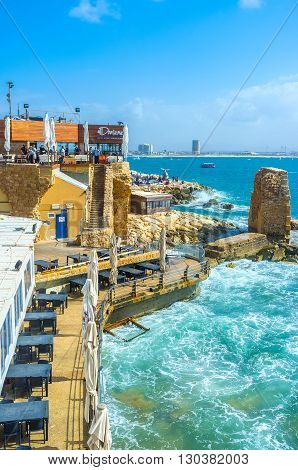 ACRE ISRAEL - FEBRUARY 20 2016: The cozy outdoor restaurant located next to the ruins of the medieval Crusader harbor on February 20 in Acre.