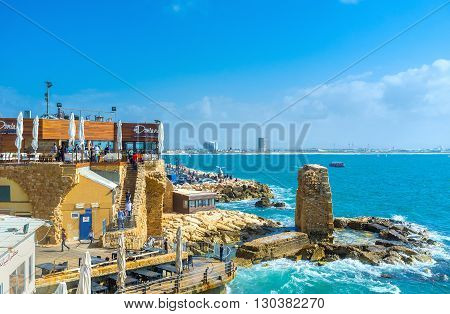 ACRE ISRAEL - FEBRUARY 20 2016: The former Crusader harbor is the place of tourist interest with various cafes and bars to relax and enjoy the seascape on February 20 in Acre.