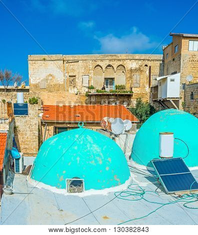 The roof of the old mosque with bright blue domes and the medieval residential buildings on the background Acre Israel.
