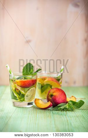 Cold fresh lemonade drink with, nectarine, lime and mint on a green wooden background