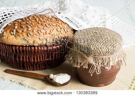 Rye bread in a wicker basket and a clay pot on a napkin on a light wooden background.