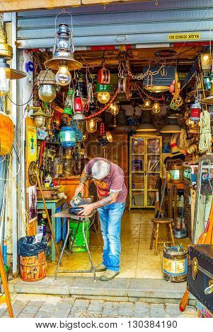 TEL AVIV ISRAEL - FEBRUARY 25 2016: The man polishes the metal detail in the workshop located in the flea market of old Jaffa on February 25 in Tel Aviv.