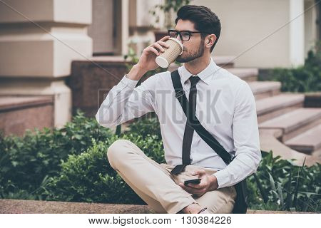 Sip of fresh coffee before working day. Confident young man in glasses drinking coffee and holding his smart phone while sitting outdoors