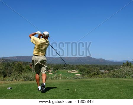 Golfer Driving Golf Ball On Beautiful Golf Course With Clear Blue Sky In The Mountains