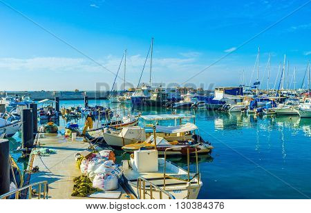 TEL AVIV ISRAEL - February 25 2016: The fishing boats and yachts in the old port of Jaffa on February 25 in Tel Aviv.