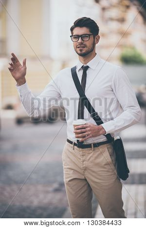 Hey taxi! Confident young man in glasses holding coffee cup and waving for taxi while walking outdoors