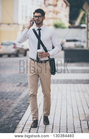 Business talk on a go. Full length of confident young man in glasses holding coffee cup and talking on mobile phone while walking outdoors