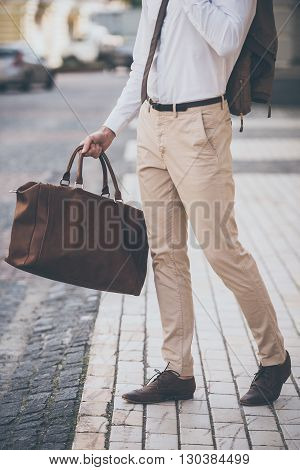 Perfect style. Part of man holding leather bag while walking outdoors