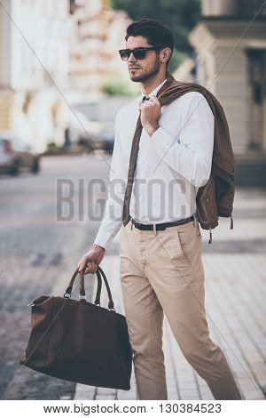 Handsome and stylish. Handsome young man holding leather bag and looking away while walking outdoors
