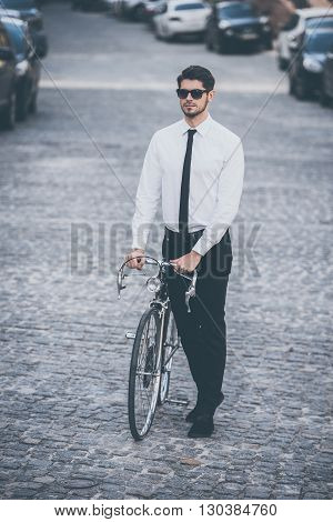 His stylish ride. Full length of handsome well-dressed young man rolling his bicycle outdoors